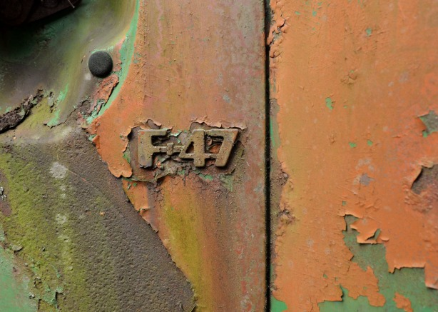 Close up of the F-47 logo on the side of a very rusty truck. Lots of oranges and browns.