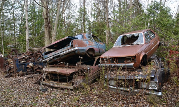 Four old cars. Two piles of two. The windshields are broken and the tires are missing. Lots of rust and broken metal.