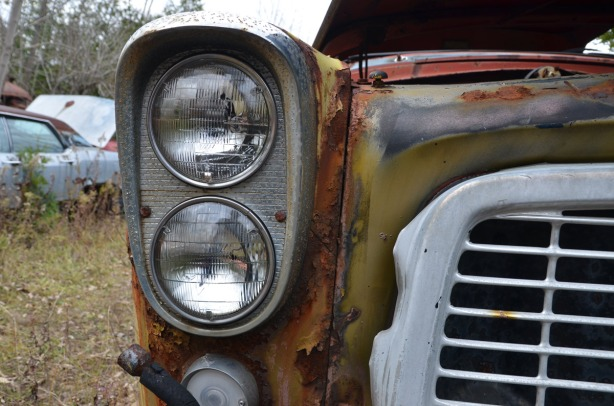 The front corner of an old yellowish green car. It has two round headlights within an oval piece of chrome.