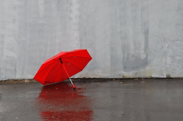 A red umbrella is open and sitting on the wet pavement beside a grey painted wall.