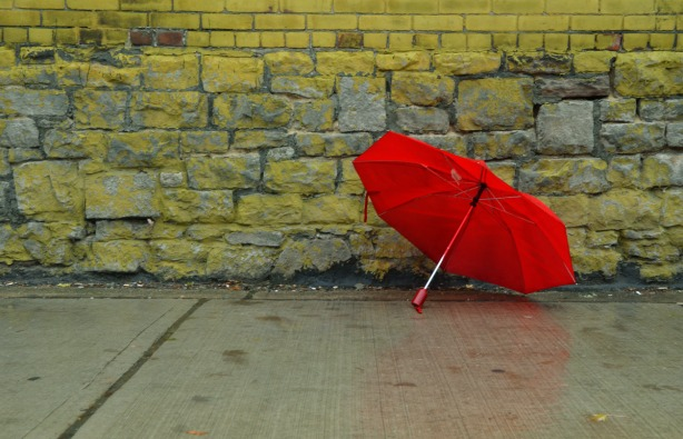 A red umbrella is beside a stone and brick wall that was once painted yellow.  The yellow paint has started to wear off.