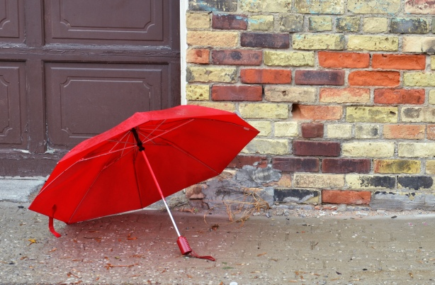 A red umbrella in front of a wall made of different coloured bricks - yellowish, orange, brown, and purple