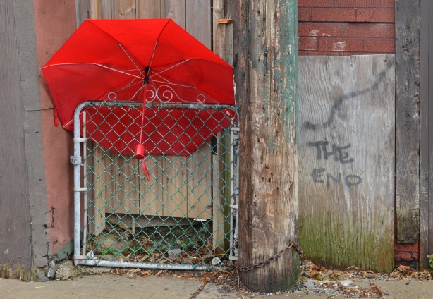 The red umbrella is wedged between the top of a chainlink gate and a wood door.