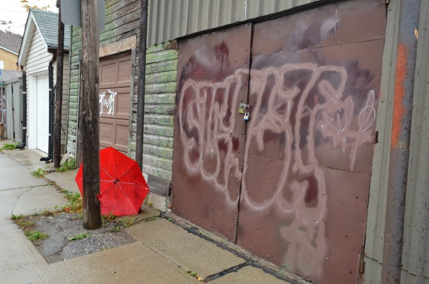 A red umbrella is wedged between two poles beside a purplish brown garage door in an alley