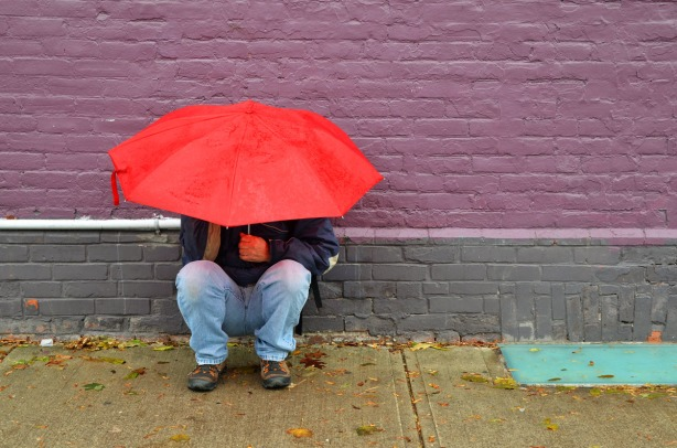 A man is crouching beside a brick wall that has been painted purple and grey.  He is holding a red umbrella over his head.