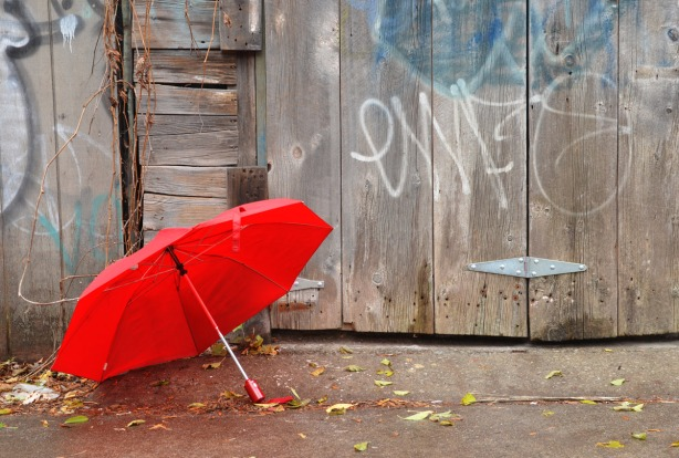 A red umbrella on the ground beside a gate made of weathered wood