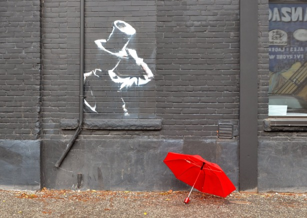 A white line drawing of a man with a top hat (upper body only) on a dark grey wall.  On the ground beside the wall is a red umbrella