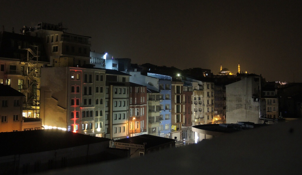 a night time view of lowrise residential buildings at night.  There is a lot of light from the street below.