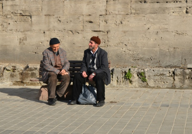 two older Turkish men sitting on a bench talking to each other.  They are dressed for cold weather