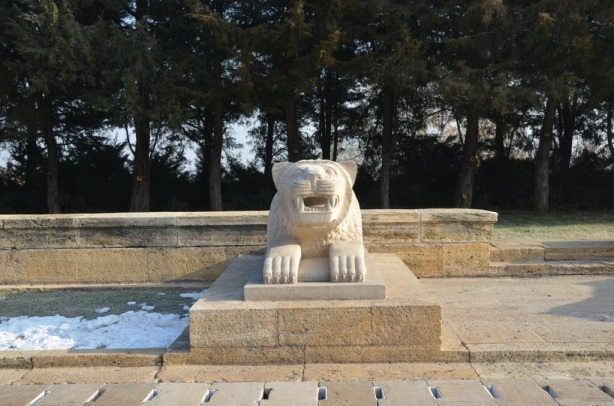stone statue of a lion who looks like he is roaring at the camera