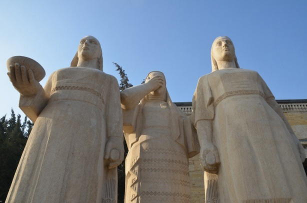 very large stone statues of 3 women who are standing