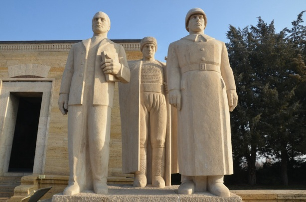 large stone statue of three men