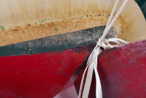 close up of a red, dark green and off-white striped hull of a sailboat.  A knotted white rope is in the photo too.