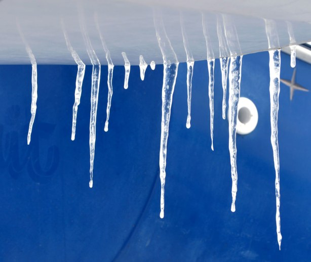icicles hanging off the side of a blue and white boat.  Close up shot.