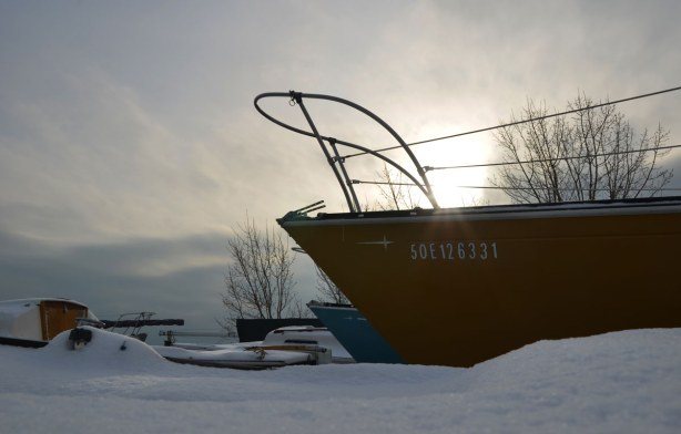 In the background the sun tries to shine through the clouds.  There is enough light that rays of sunshine bounce off the yellow hull of a boat that is in the foreground.