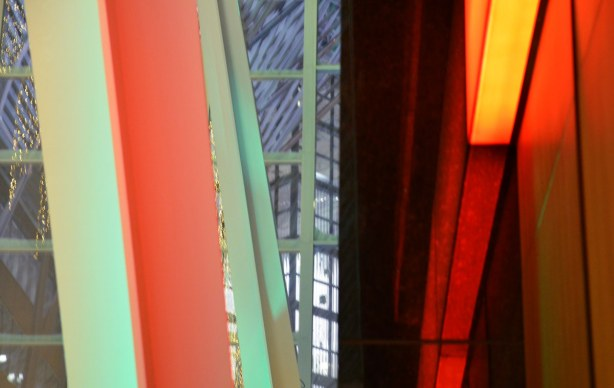 abstract looking picture of horizontal shapes in oranges, greens and purples.  The photo is of part of a wall, a metal support beam, and a glass wall.