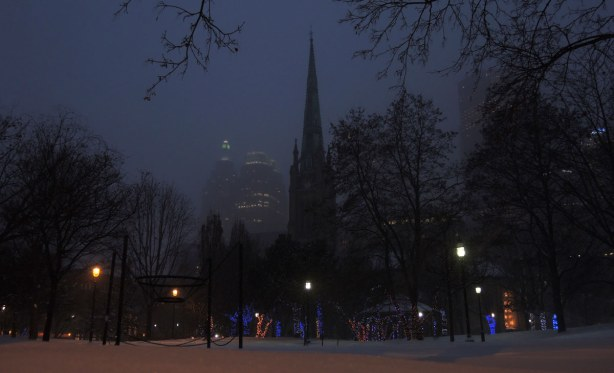 looking across a snowy St. James Park towards the cathedral whose steeple is partially obscured by trees.  Late afternoon.  Part of the Toronto skyline can be seen in the background.