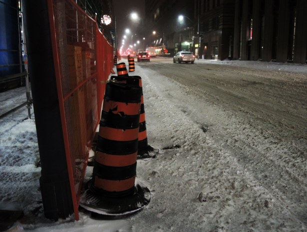 Black & orange construction cones along side a plastic orange fence around a construction site at the side of the road.  Traffic stopped at a stoplight in the distance.