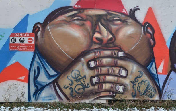 graffiti picture of the face, shoulders and arms of a fat man. The backs of his hands have tattos of a bicycle and a cupcake.