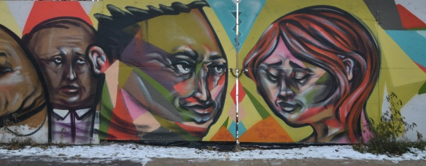 Three faces graffiti. Two men's heads on the left and a woman's head on the right. They are painted on a wood gate that is closed and locked with a chain.