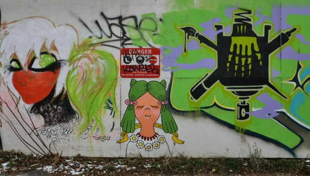 Graffiti of two women's heads. There is also a red and white danger sign in the middle of the picture.