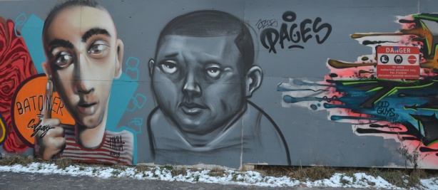 graffiti picture of the head and shoulders of two men. The one of the right is in shades of grey while the one on the left is a more natural colour.