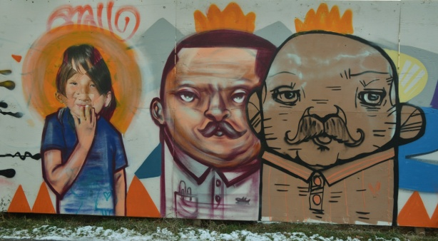 graffiti picture of the upper bodies of 3 people, 2 men and a girl. The girl seems to have an orange halo around her head. The men have orange crowns on their heads.