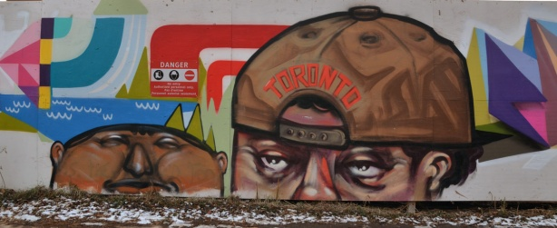 Street art picture of 2 male heads. One is wearing a brown baseball cap backwards. The word Toronto is written on it in orange letters.