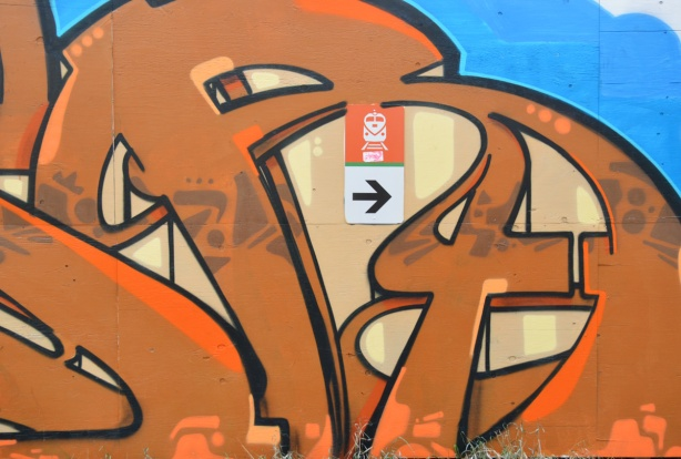 Part of an orange and beige graffiti tag. It surrounds a small sign that points to the entrance to the train station.