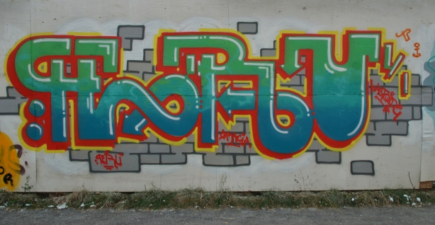 graffiti tag - stylized letters forming the word Peru in green, blue and red. Some grey bricks have been painted behind the letters.