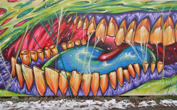 large graffiti picture of a close up of a mouth interior showing many orange teet, a blue tongue and purple gums.