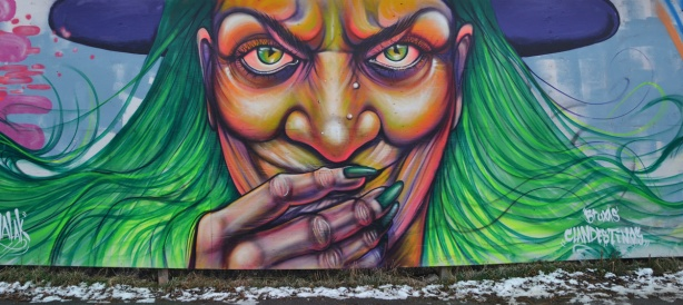 graffiti of a witch's face. She has green eyes and green hair. She is wearing a purple hat. Her boney hand is in front of her mouth so you can see her long green finger nails.