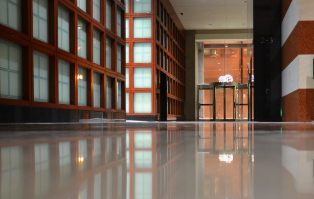 A wall and its reflection in the very polished and shiney floor.  The wall looks like a grid of brown wood surrounding pale blue glass squares.