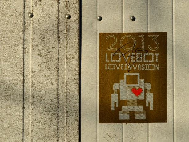 gold coloured poster on a dirty light grey garage door.  The poster says 2013 Lovebot Loveinvasion.  It has a picture of a light grey robot on it, with a red heart.