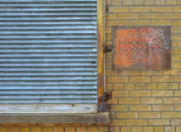An old metal sign saying No Authorized Parking has rusted badly.  It is on a yellow brick building.  Beside it is a blue coloured metal screen covering a window.