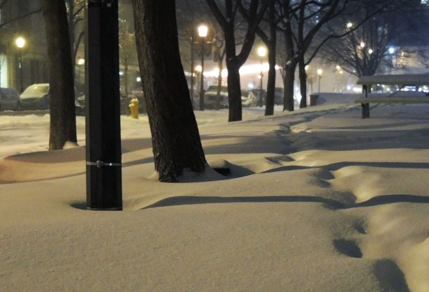 Night time.  Fresh snow on the ground with only one set of footsteps walking through it.   There are a number of trees along the side of sidewalk and they cast shadows over the snow.