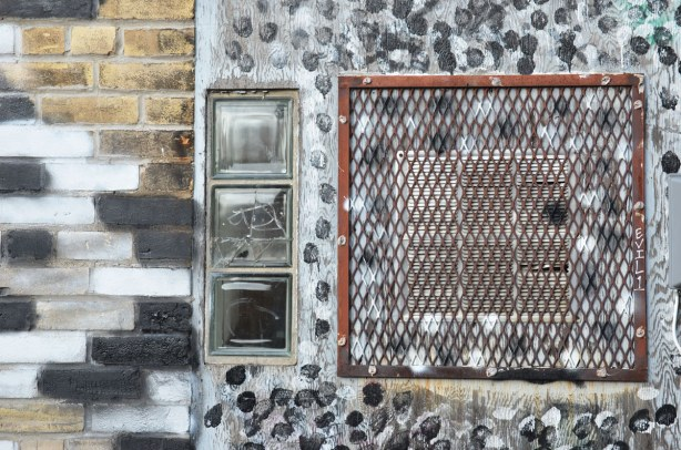 Three small windows arranged vertically beside a rusted metal grille covering an air vent.  Black and white splotches have been painted around the window.