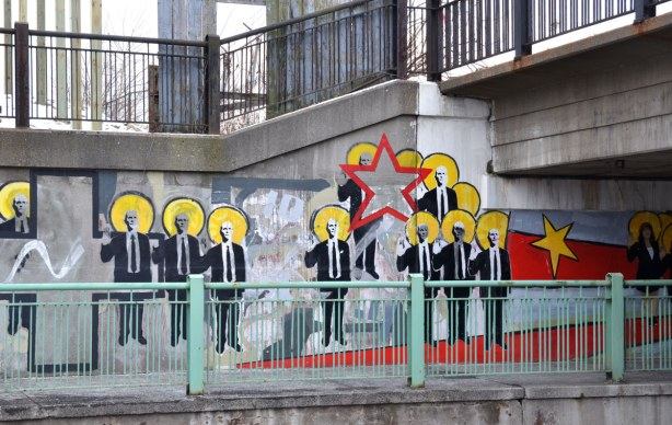 part of the mural showing many men in suits, a yellow star and a red star.