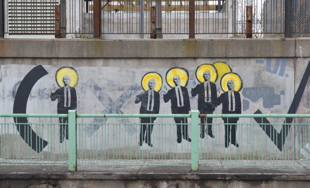 men in suits forming part of a mathematical equation.  A multiplication sign and part of a long division sign.