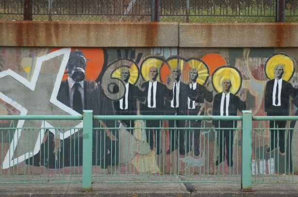 part of the suitman mural taken a couple of years ago.  The letter X, the number 6, a man wearing a gas masks plus 6 men wearing black suits and ties.  They have yellow halos around their heads.