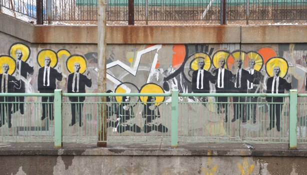part of the suitman mural - many men in suits standing in a line.   Three sitting women are in the middle.