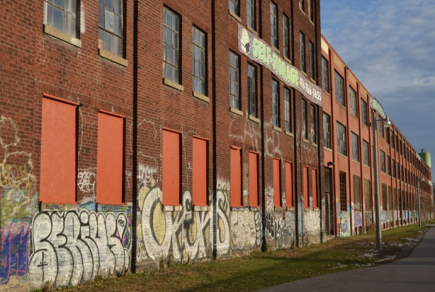 Three storey brick factory building.  The windows in the lower storey are covered with orange wood. There is graffiti along the lower five or six feet of the building.