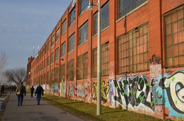 Looking north along the side of the old Viceroy rubber factory building.  A red brick building with large windows.  There is graffiti on the bottom five or six feet of the building.