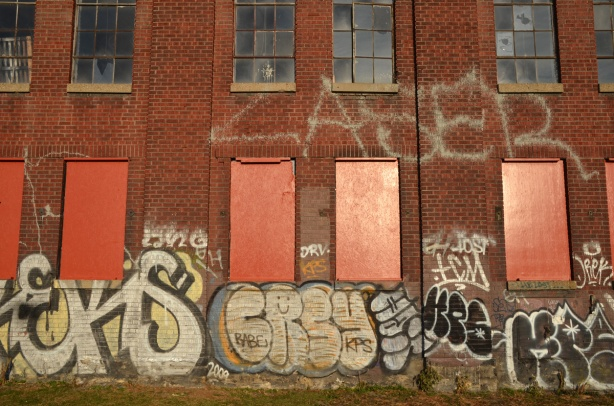 bottom two storeys of a red brick factory.  The lower storey has the windows boarded up and painted orange.  There are graffiti tags along the bottom of the building.