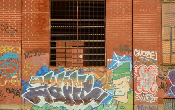 An open window covered with metal bars and a metal screen.  Graffiti on the walls too.