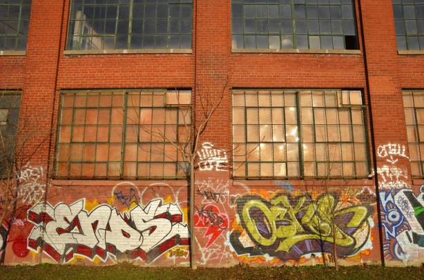 The sun is shining on a red brick building with large windows.  Graffiti tags are on the wall.