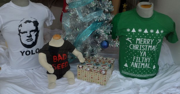 A window display in a T-shirt shop.  THere is a T-shirt with a picture of ROb FOrd with the word yolo printed on it.  There is a black toddler onsie with the words Bad Seed written in red.  There is a green T-shirt with the words Merry Christmas Ya Filthy Animal written on it.