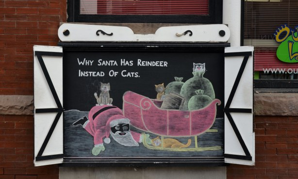 A drawing on a chalk board of Santa trying to get a hold of a cat that is hiding under his sleigh.  The words on the board say Why Santa has reindeer instead of cats.