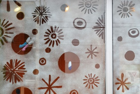 The window of the store 'Come as You Are' has been covered with a layer of fake snow.  THere are clear circles in the snow with vibrators hanging in them.  There are also some snowflake shaped clear spots.