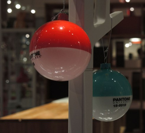 Two christmas tree balls.  Both are white on the bottom half and both are pantone colours on the top - one is red and the other is light blue, pantone universe color 15-5519